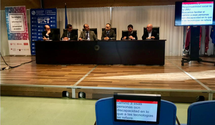 A panel of speakers is seen in a congress, a monitor with the simultaneous transcription of Ability Connect and a tablet in which the text is also being received