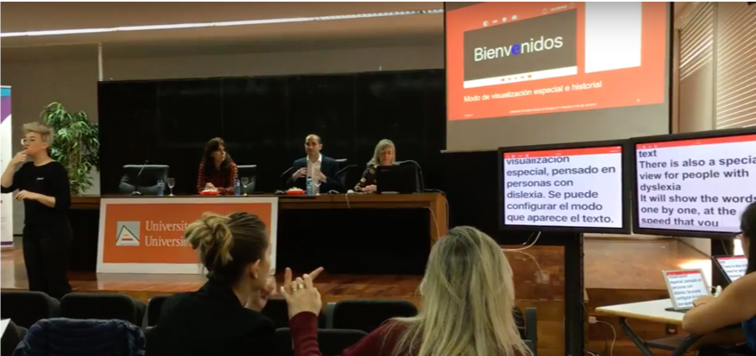 A panel of speakers on a day where two monitors can be seen with the transcript of what happens in Spanish and English with Ability Connect